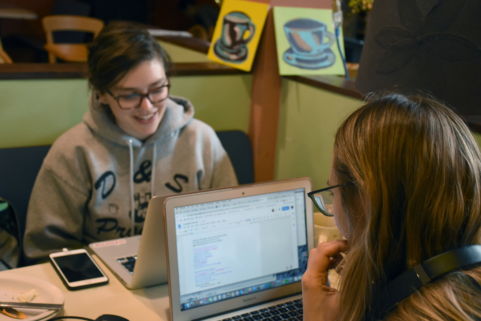 Julie Larsen works on lyrics for comedic music video with her Derby co-founder and Second Floor president, Kellie Hahn, on Sunday, March 24, 2019 in Webster's Bookstore Cafe. In March of 2018, Derby, Penn State's only all-female comedy troupe, was founded by Julie Larsen, Karina Ciocca, and Kellie Hahn – three women who had felt the isolating effects of being a female comedian in State College.