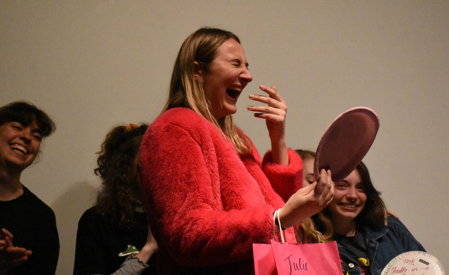 """Julie Larsen receives the """"Dumb Bitch"""" award from her fellow Derby troupe members as her senior farewell gift at their last show of the semester, Derby Presents: Space Cowboy, on Friday, April 12, 2019 in 113 Carnegie. Derby has two showcases per semester to showcase the growth and content written by Derby members."""