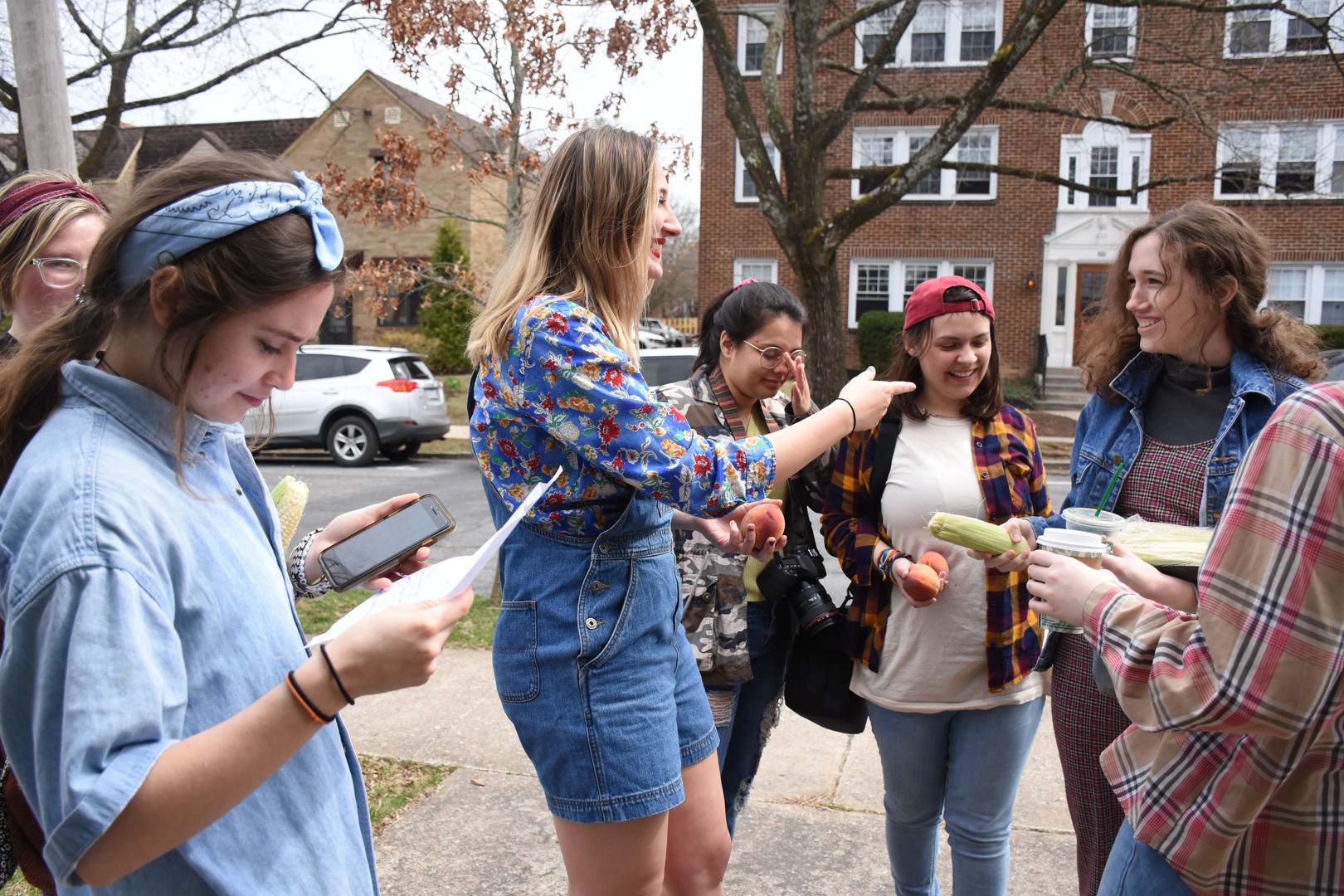 """Members of Derby prepare for a day of shooting their comedic music video """"Georgia Peach, Pennsylvania Corn Cob"""" on Sunday, April 7, 2019 on Fairmount Avenue, State College. Derby was created in order to provide a supportive and safe space for women to write and perform comedy. Left to right, Molly Shilling, Kristen Nodell, Julie Larsen, Chelsea West, Rachel Hobbs, Torin Cronin, and Kellie Hahn."""