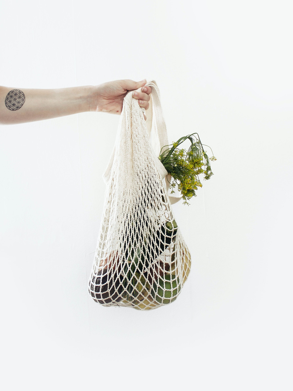 Person holding reusable bag with vegetables