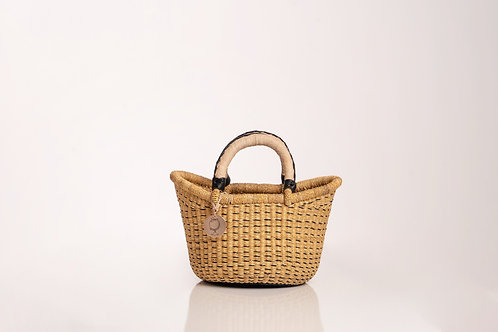 Small straw handwoven basket with leather handles. Sustainable home decor