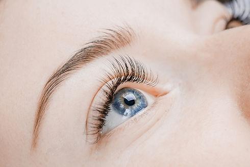 Eyelash extension procedure. Beautiful female eyes with long lashes, closeup..jpg