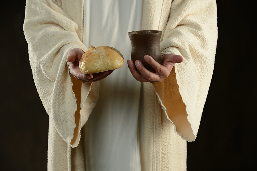 Jesus holding and offering the bread and