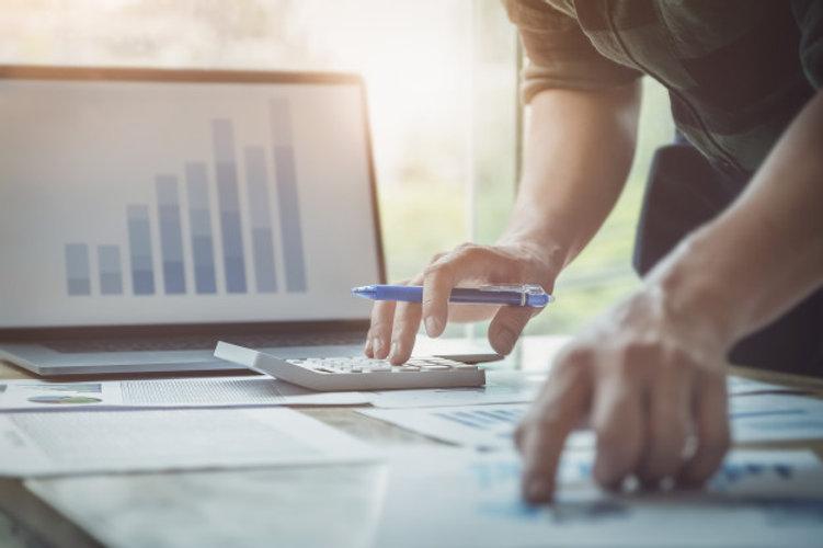 business-man-using-calculator-review-bal