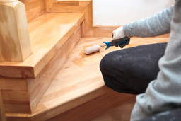 painter-paints-varnish-wooden-board-by-r