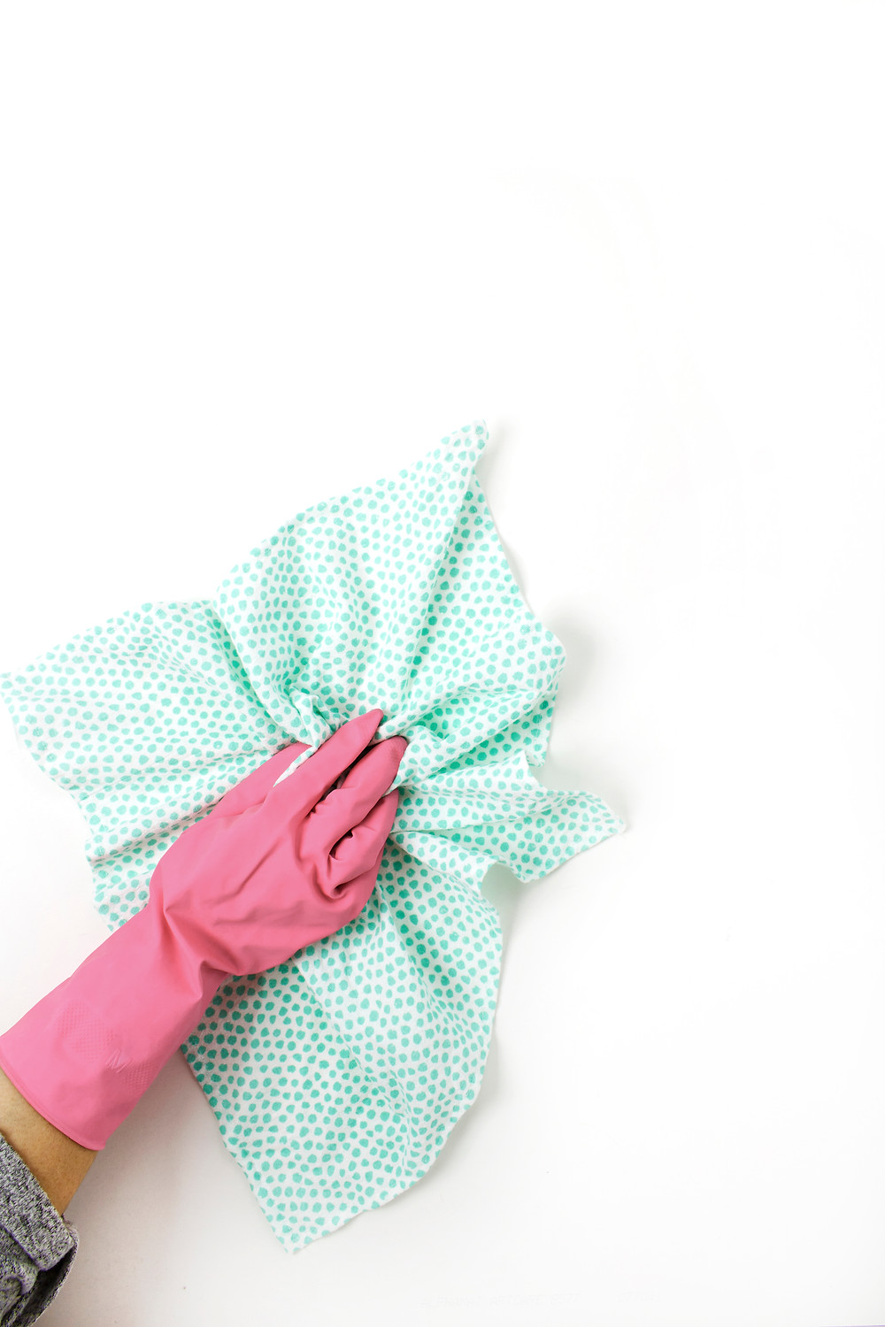 a gloved hand using a cleaning rag