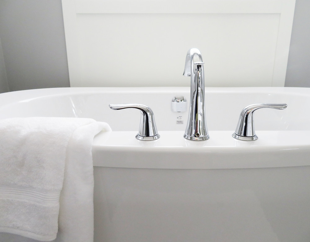 a clean bathtub with white towel draped on side