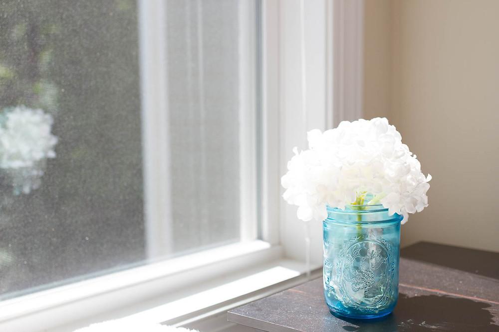 a mason jar of white flowers beside a window
