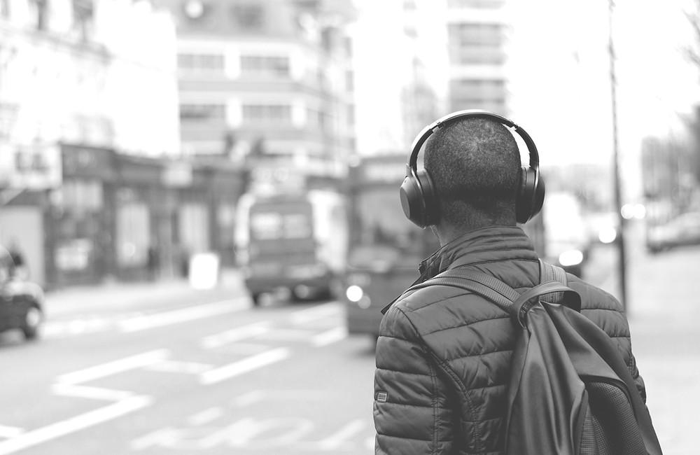 Homem de costas, de frente para uma avenida, com fone do tipo headphone, em suas costas uma mochia.