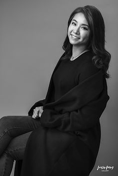 Portrait Photography in Hong Kong of a smiling woman on a chair in black and white