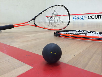 Squash Court mit Ball und Schläger, daneben Tischtennis