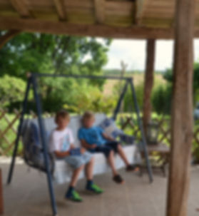 children on a swing seat on a porch