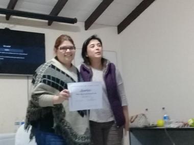 Presentando certificación, organizadora Mara Moreno.