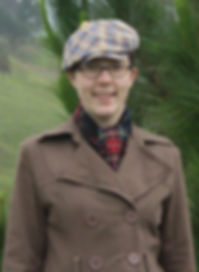 Maria Lord wearing a brown pea coat and plaid hat and scarf, with a pine tree and mountains in the background