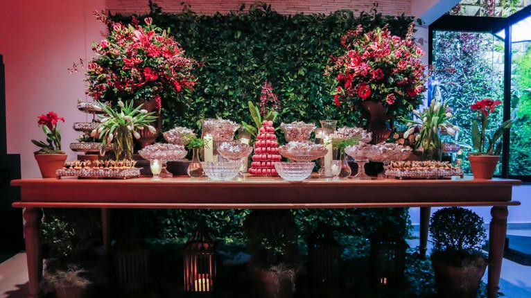 Mesa de doces com flores vermelhas.