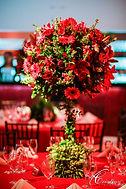 Arranjo feito com gloriosa, rosas e outras flores na paleta.