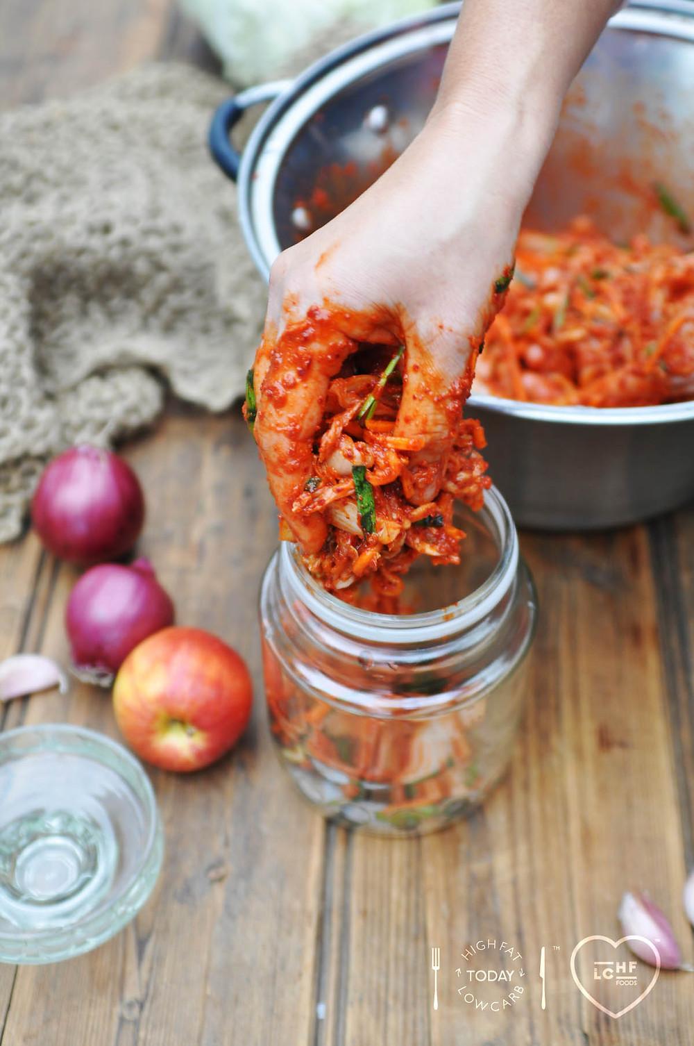 Pressing Kimchi mixture into glass jars
