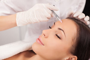 Close up of hands of expert beautician injecting botox in female forehead. The woman closed her eyes