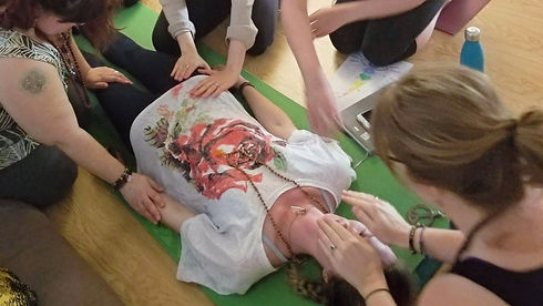 Woman laying down, receiving energy from other women