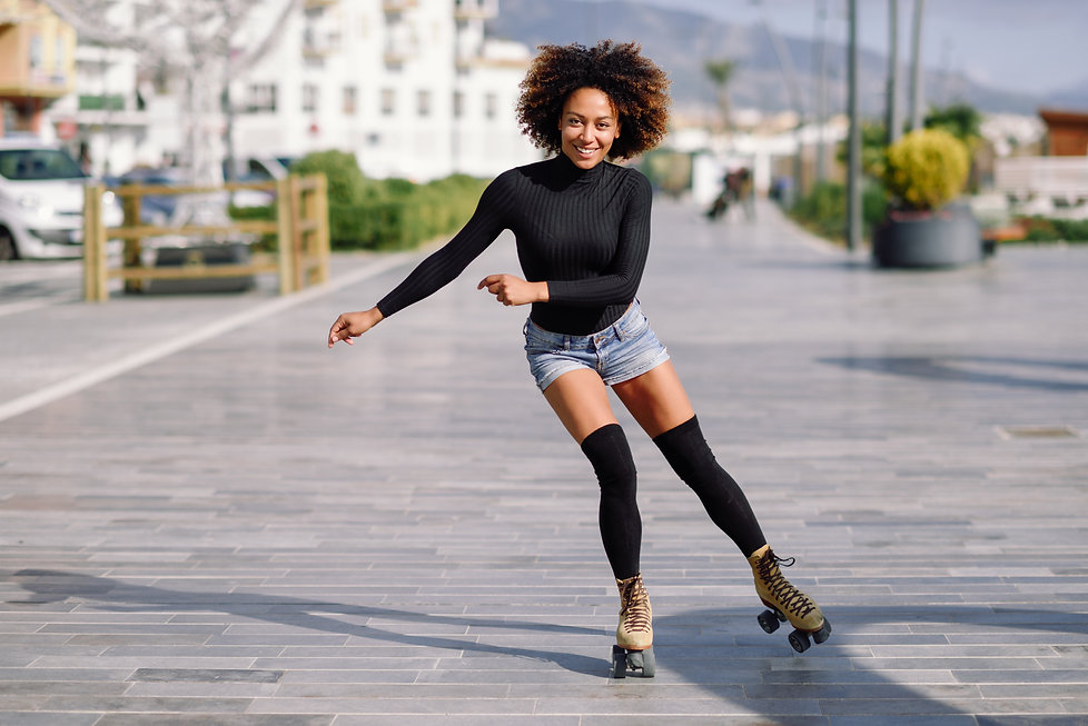 Young fit black woman on roller skates r