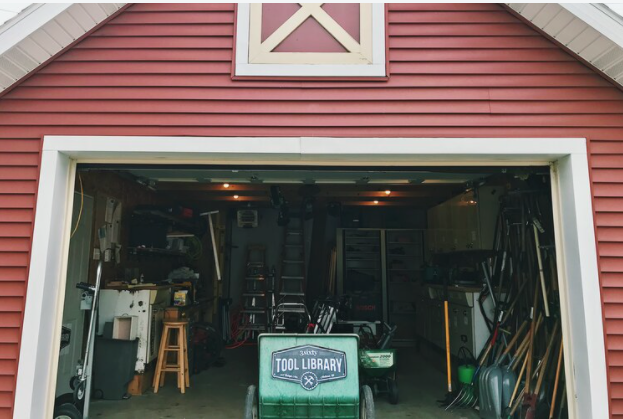 A barn door is open with a variety of tools available for use.