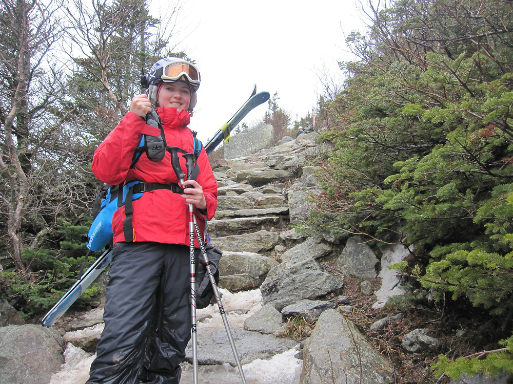 Abby hiking a rocking section to Tuckerman's Ravine with pack and skis