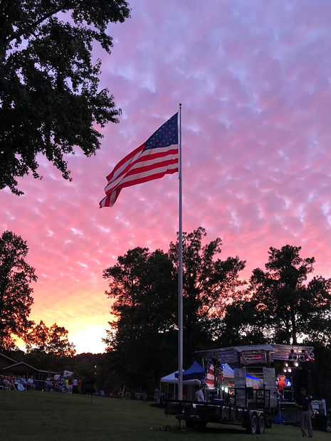 Picture of American flag flying in front of a beautiful sunset