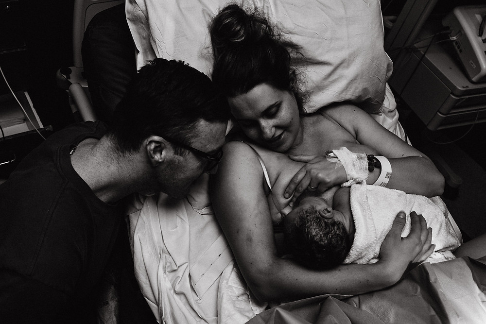 father leans on mums shoulder as she breastfeeds their newborn son.