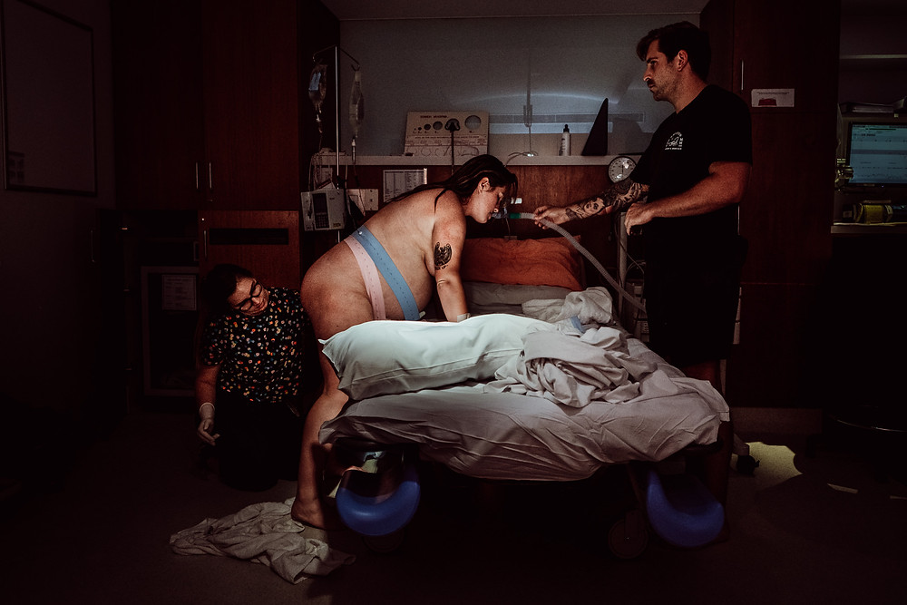 Woman labouring over a bed as her partner helps hold the gas and her midwife assess her
