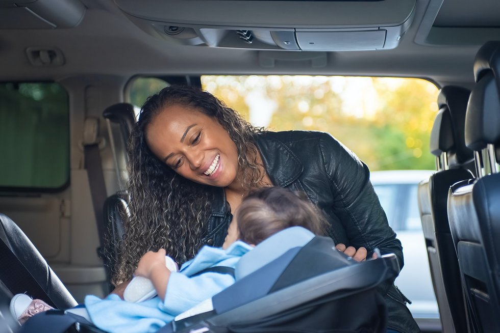 Mother smiling at baby in car seat.
