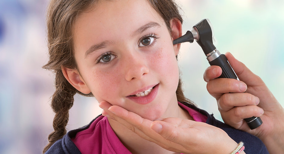 physician checking patient's ear using o