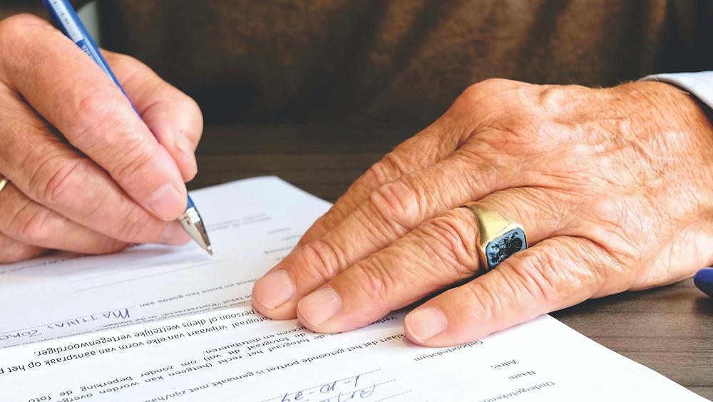 Personne agée signant un document attestant de son consentement