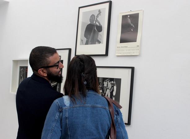 Visiteurs devant photos de musiciens