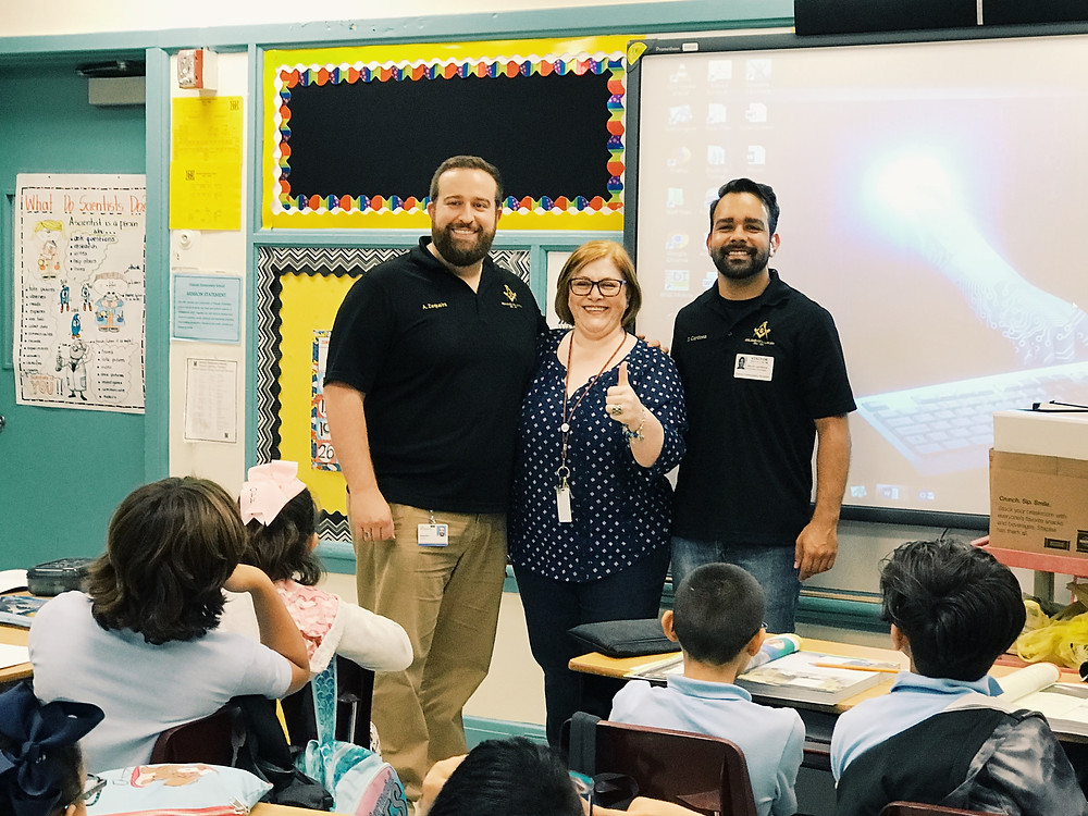 Brothers presenting Mrs. Matilde Silva with school supplies
