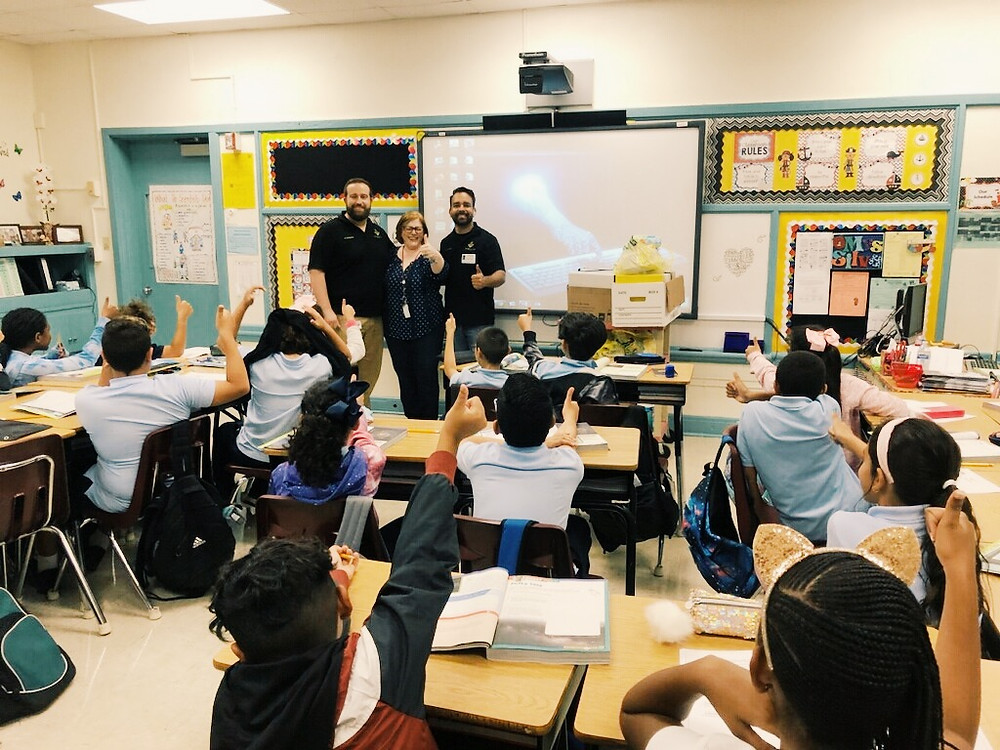 Brothers Alejandro Zequeira & David Cardona present supplies to teacher and students.