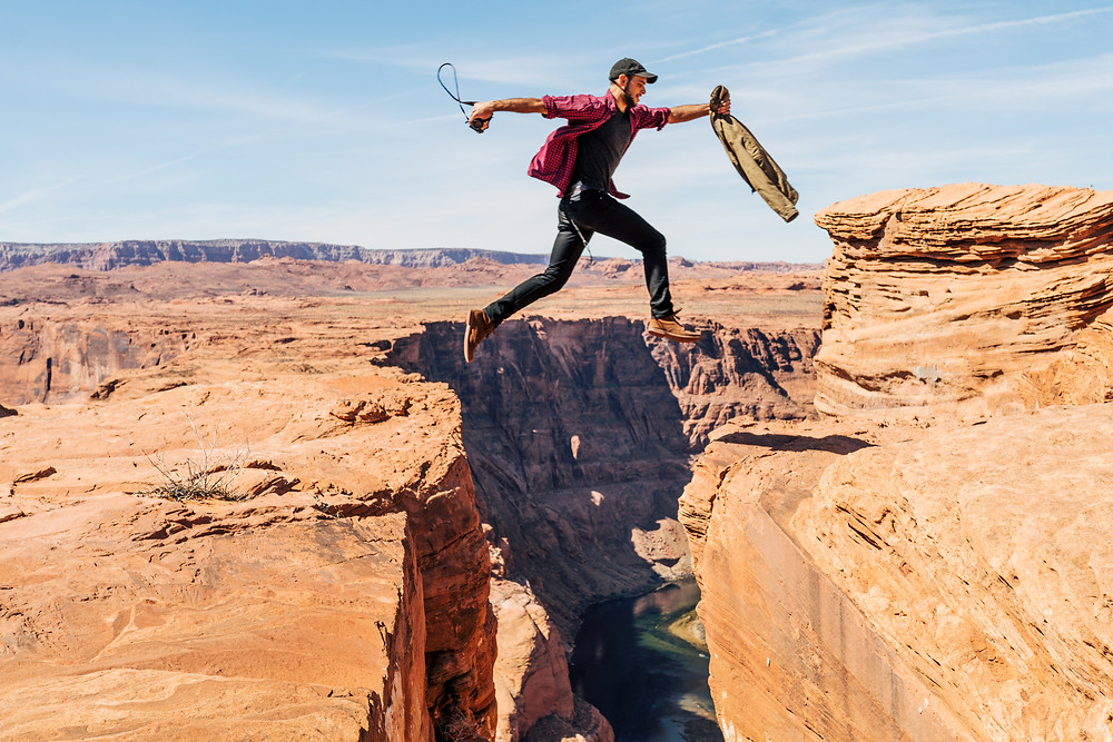 Man leaping over a rocky chasms
