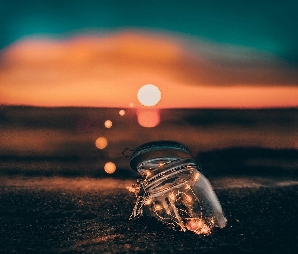 A jar of fairy lights partially buried on a sunlit beach