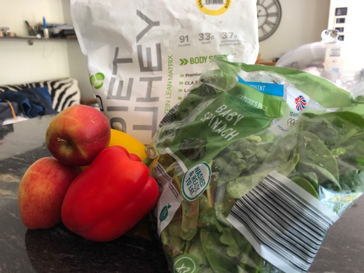 A collection of fresh peppers, apples, bag of spinach and protein powder on a tabletop