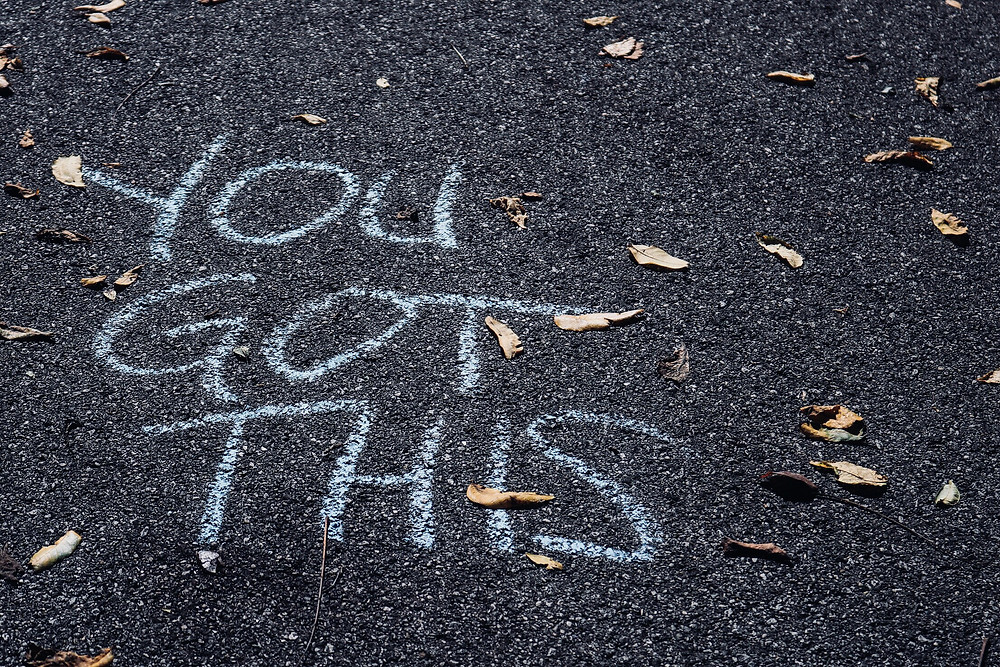 "White chalk message ""You Got This"" written on asphalt pavement"