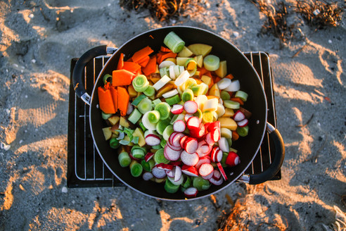Chopped fresh seasonal vegetbles sit in a pot on the beach ready to be cooked on the fire outside the van.