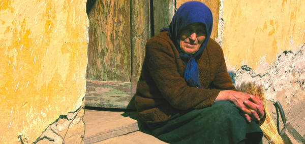 Elderly Romanan lady sits on her doorstep.