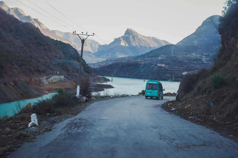 Commuter minibus by Lake Koman in the Albanian Alps - From Rust To Roadtrip documentary