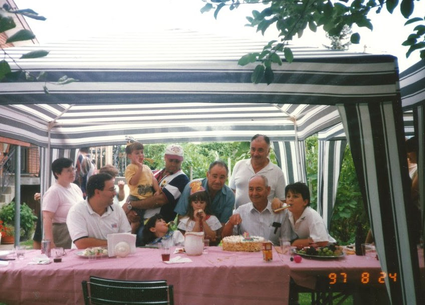 A family gathered under a green and white tent, at a table covered in a pale red tablecloth. They are celebrating a birthday in summer, in a backyard. The photo was taken on August 24, 1997.