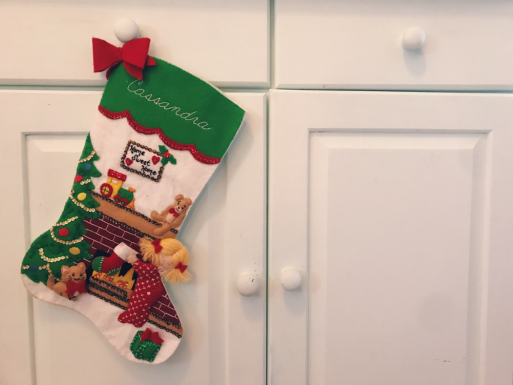 "A felt stocking hanging on the knob of a light blue cabinet. The stocking has the name ""Cassandra"" stitched at the top. It shows the scene of a blonde-haired girl putting her stocking up on the mantle of her fireplace, beside a Christmas tree and cat."