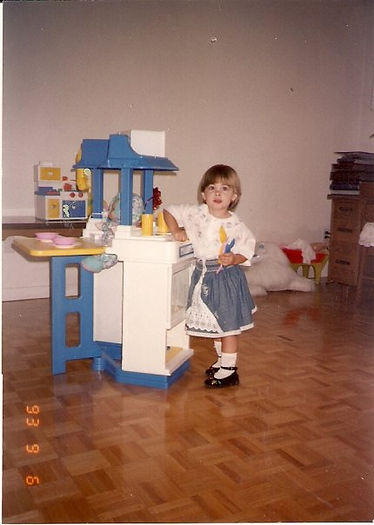 A young girl in a white and blue skirt and top stands at her play kitchen, holding a plastic spoon. She has a mushroom cut. This photo was taken in 1993.