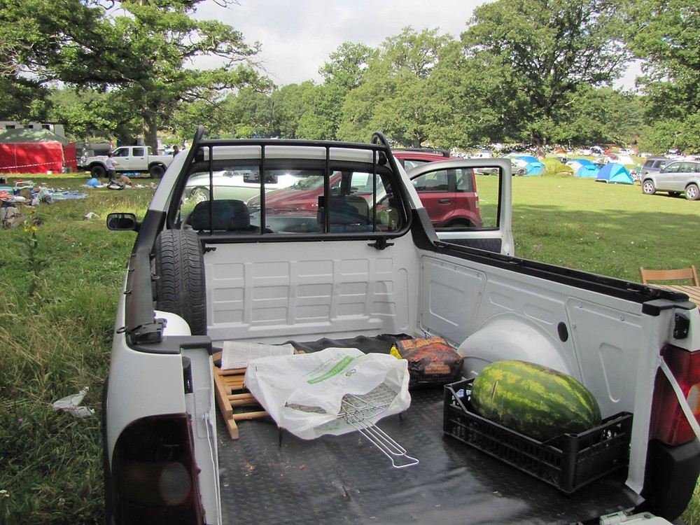 A white pick-up truck with the back open. There's a watermelon in the trunk and, in the distance, there are various other cars and tents set up in a green, grassy area.