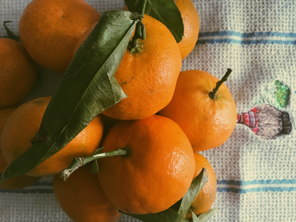 A pile of clementines, some with leaves and stems, on a blue and white dish rag.