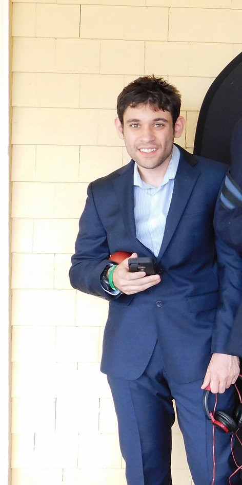 Image of Stephen Gordon, wearing a blue suit with a light blue collared dress shirt, smiling at the camera as he holds his phone and a small ball in his right hand.
