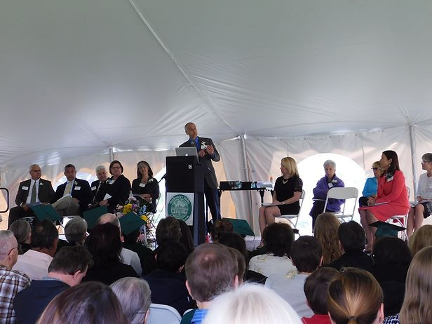 Image of Daniel Habib speaking at the podium under the tent; members of the BHMA Board are visible on stage.