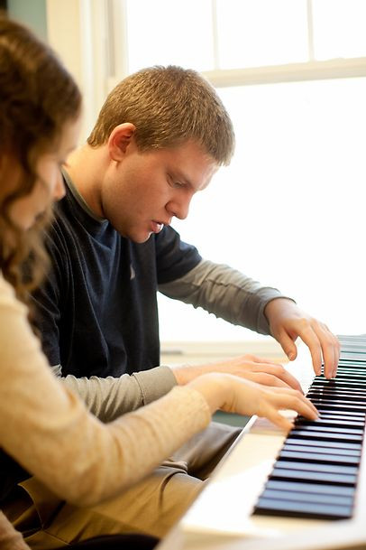 Image of Brian Krutzler, wearing a navy blue t-shirt over gray long sleeves, looking pensively at the piano keys as he is guided by Music Instructor Alyson Grammo.